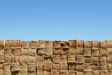 hay bales wall against blue sky poster