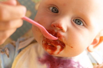 a little baby eating from a spoon