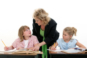 teacher helping child in classroom