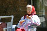 senior lady eating outside poster