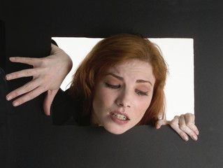 redheaded woman climbing out of a black box