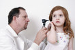 doctor checking little girl's ear with a stethosco