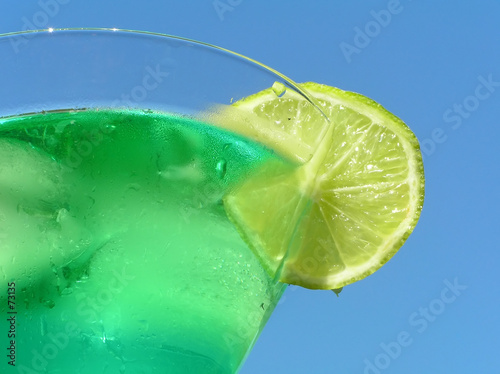 green cocktail with slice of lemon