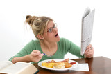 young woman reading newspaper at breakfast poster
