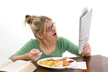 young woman reading newspaper at breakfast