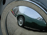 old english car reflected in hubcap of another poster