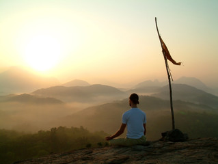 man meditating at sunrise