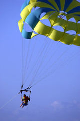 male parasailing against blue sky