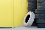 stack of tires against yellow wall poster