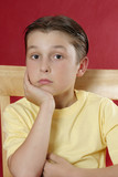 sitting boy resting head on hand poster
