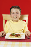child at table with plate of food poster