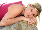 beautiful young woman resting on a large rock poster