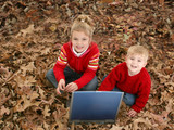 brother and sister sitting in leaves with laptop poster