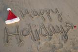 happy holidays written in sand