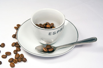 tight closeup of espresso cup and saucer with beans