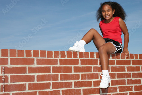 beautiful seven year old girl on brick wall