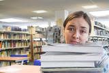 female student in a library - too much work poster