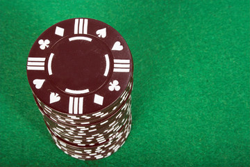 brown pile of casino chips over green
