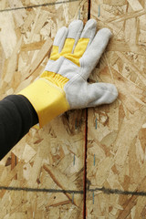 gloved hand and plywood wall