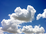 white puffy clouds against bright blue sky poster