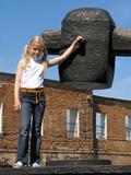 girl near large hammer poster