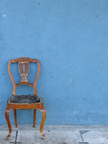 wooden chair alone with blue background poster