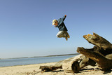jumping boy on the spring beach poster