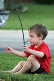 young boy playing with sticks poster