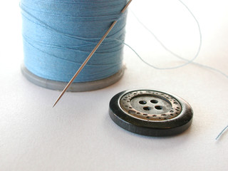 spool of thread with button and needle