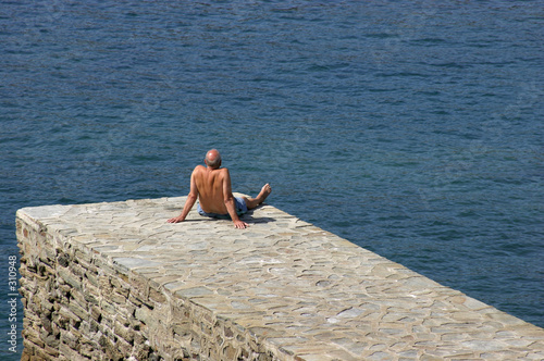 man sunbathing on waters edge near beach