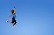 young woman jumping over a blue sky.
