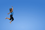 young woman jumping over a blue sky. poster