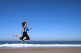 young woman runing and jumping in the beach poster