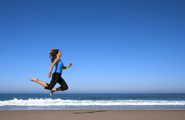young woman runing and jumping in the beach