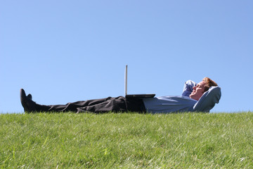 laptop on businessman on grass