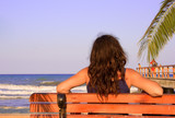 female relaxing on a beach bench poster