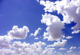 blue sky with puffy white clouds poster