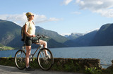 sporty woman on a bike trip in the mountains poster