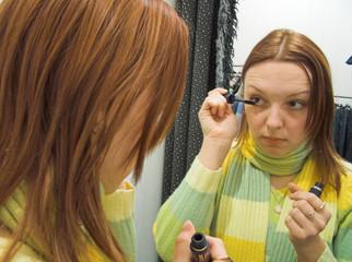 the girl paints eyelashes