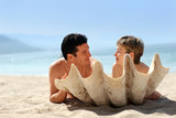 romantic couple on the beach behind the seashell