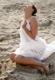 woman in white clothes sitting on the beach poster