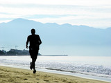 man running on the beach in the morning poster