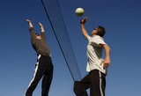 young men hitting the ball over the net poster