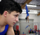 young gymnast watching his friends compete poster