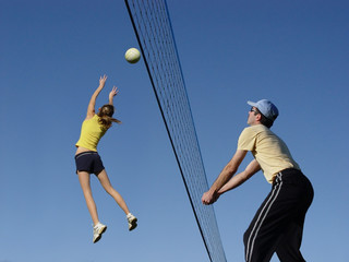 a girl and a man playing volleyball