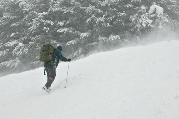 climber going for the top in a snow storm