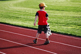 boy with a checked flag walking on a racetrack poster