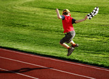 boy with a checked flag jumping on a racetrack poster