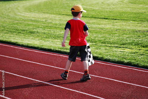 poster of boy with a checked flag walking on a racetrack