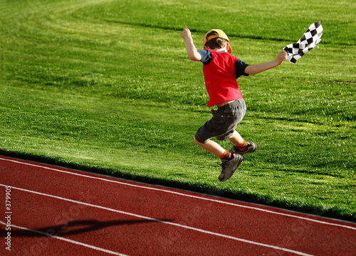boy with a checked flag jumping on a racetrack